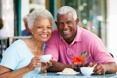 Pares mayores que gozan del bocado en el café al aire libre Imagenes de archivo