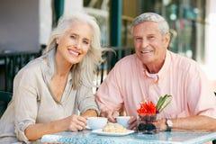 Pares mayores que gozan del bocado en el café al aire libre Fotografía de archivo