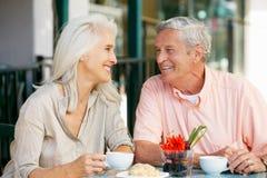 Pares mayores que gozan del bocado en el café al aire libre Fotos de archivo