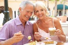 Pares mayores que gozan del café y de la torta Fotos de archivo