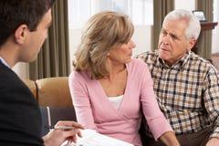 Pares mayores que hablan con el consejero financiero Imagenes de archivo