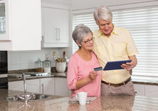 Pares mayores que hacen compras en línea con PC de la tableta Imagenes de archivo