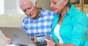 Pares mayores que hacen compras en línea usando el ordenador portátil con la tarjeta de crédito en la sala de estar almacen de metraje de vídeo