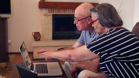 Pares mayores que hacen compras en línea usando tarjeta de crédito en el ordenador portátil almacen de metraje de vídeo