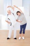 Pares mayores que hacen estirando ejercicio Fotos de archivo libres de regalías