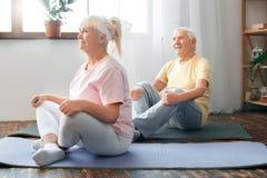 Pares mayores que hacen estirar de la actitud de la mariposa de la atención sanitaria de la yoga junto en casa Imágenes de archivo libres de regalías