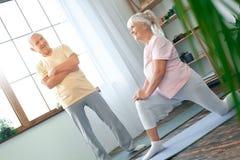 Pares mayores que hacen la atención sanitaria de la yoga junto en casa que estira la pierna Foto de archivo
