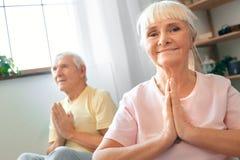Pares mayores que hacen la atención sanitaria de la yoga junto en casa que sienta actitud namaskar Foto de archivo libre de regalías