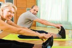 Pares mayores que hacen los ejercicios interiores Fotografía de archivo