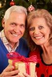 Pares mayores que intercambian los regalos de la Navidad Fotografía de archivo libre de regalías