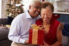 Pares mayores que intercambian los regalos de la Navidad en casa Foto de archivo