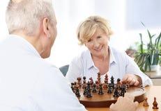 Pares mayores que juegan a ajedrez Imagenes de archivo
