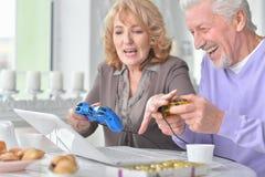 Pares mayores que juegan al juego de ordenador con el ordenador portátil mientras que bebe t Fotos de archivo