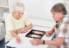 Pares mayores que juegan a backgammon Imágenes de archivo libres de regalías