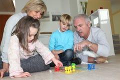 Pares mayores que juegan con los nietos Imagen de archivo