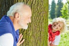 Pares mayores que juegan escondite en naturaleza Imágenes de archivo libres de regalías