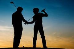 Pares mayores que juegan a golf en la puesta del sol Foto de archivo libre de regalías