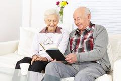 Pares mayores que leen un libro Imagenes de archivo