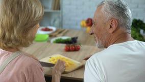 Pares mayores que ligan mientras que cocina la cena en la cocina casera, familia feliz metrajes