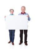 Pares mayores que llevan a cabo el cartel en blanco Imagenes de archivo