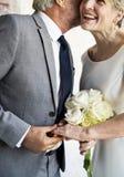 Pares mayores que llevan a cabo las manos juntas alegres fotografía de archivo