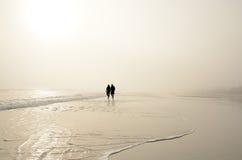 Pares mayores que llevan a cabo las manos que caminan en la playa que disfruta de salida del sol Foto de archivo