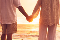 Pares mayores que llevan a cabo las manos que gozan en la puesta del sol Imágenes de archivo libres de regalías