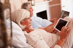 Pares mayores que mienten en cama usando los dispositivos de Digitaces fotos de archivo libres de regalías