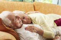 Pares mayores que mienten en Sofa At Home Fotos de archivo
