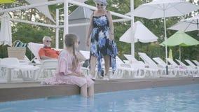 Pares mayores que mienten en sunbeds cerca de la piscina en el fondo Poco muchacha divertida que se sienta al borde de la piscina almacen de metraje de vídeo
