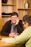 Pares mayores que miran el folleto Fotos de archivo libres de regalías