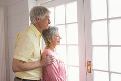 Pares mayores que miran hacia fuera su ventana Imágenes de archivo libres de regalías