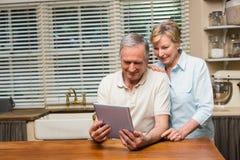Pares mayores que miran la PC de la tableta junto Imágenes de archivo libres de regalías