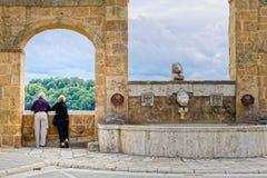 Pares mayores que miran la visión desde el pueblo de Pitigliano Fotografía de archivo libre de regalías