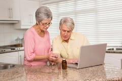Pares mayores que miran para arriba la medicación en línea Fotografía de archivo libre de regalías