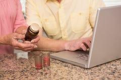 Pares mayores que miran para arriba la medicación en línea Fotos de archivo