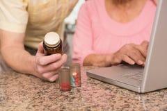 Pares mayores que miran para arriba la medicación en línea Foto de archivo libre de regalías