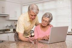 Pares mayores que miran para arriba la medicación en línea Imagenes de archivo
