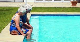 Pares mayores que obran recíprocamente con uno a en el poolside almacen de video