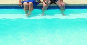Pares mayores que obran recíprocamente con uno a en el poolside metrajes
