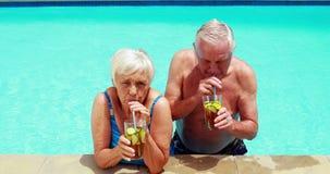 Pares mayores que obran recíprocamente con uno a mientras que comiendo vidrios de té helado almacen de metraje de vídeo