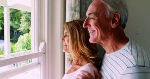 Pares mayores que obran recíprocamente con uno a mientras que mira hacia fuera de la ventana almacen de video
