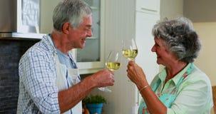 Pares mayores que obran recíprocamente mientras que comiendo vino en la cocina 4k metrajes