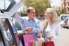 Pares mayores que ponen bolsos en coche Imagen de archivo libre de regalías