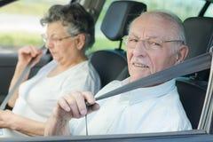 Pares mayores que ponen en sus cinturones de seguridad fotografía de archivo libre de regalías