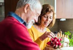 Pares mayores que preparan el alimento en la cocina foto de archivo