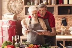 Pares mayores que preparan el almuerzo con el libro de la receta fotografía de archivo