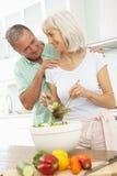 Pares mayores que preparan la ensalada en cocina moderna imagenes de archivo