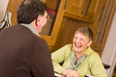 Pares mayores que ríen junto en cocina Fotografía de archivo libre de regalías