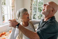 Pares mayores que ríen y que tienen baile de la diversión foto de archivo libre de regalías